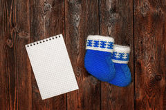 Blue hand made crochet baby booties and blank notebook, copyspace Stock Images