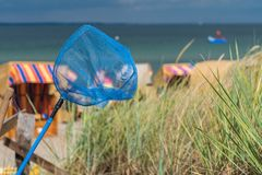 Blue hand net on the beach. Roofed wooden chairs on sandy beach in Background. Travemunde, Germany Stock Image