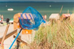 Blue hand net on the beach. Roofed wooden chairs on sandy beach in Background. Travemunde, Germany Stock Photos