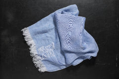 Blue Hand Towel with White Fringes on Dark Surface. A blue hand towel with white fringes placed at center of a dark surface Stock Photos