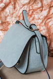 Blue handbag, delicate and feminine. Trouser suits and dresses Royalty Free Stock Image