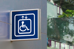 Blue Handicap Elevator Sign with Blurred Glass Bac. Kground, Closeup, Right Copy space Stock Photo