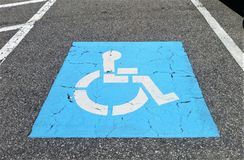 Blue Handicapped Symbol on Parking Pavement. Bright blue handicapped symbol painted on parking spot pavement Royalty Free Stock Image