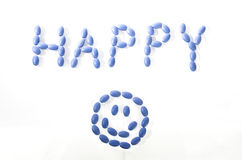 Blue Happy Pills. Blue pills spelling word Happy with smiley face Stock Photography