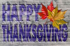 Blue Happy Thanksgiving written on wooden board background with colorful leaves. Close Stock Images