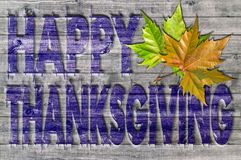 Blue Happy Thanksgiving written on wooden board background with leaves. Close Royalty Free Stock Image