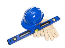 Blue hardhat with level and leather gloves Stock Photos