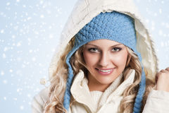 Blue hat on a blond girl. Winter shot of a young pretty woman wearing a light blue hat and white sweater and scarf over white Royalty Free Stock Images