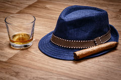 Blue hat with cigar and expensive drink of whisky or rum on wooden floor Royalty Free Stock Photos