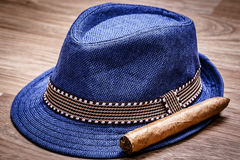 Blue hat and cigar on wooden floor, smoke concept Stock Photography