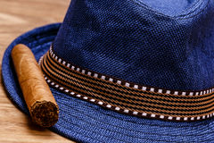 Blue hat and cigar on wooden floor, smoke concept Stock Image