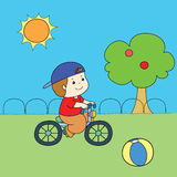 Blue hat red shirt boy riding bicycle  Royalty Free Stock Photography