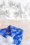 Blue hat Santa Claus on wooden table on background of snow-covered pine branches. Royalty Free Stock Image