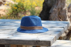 Blue hat on the woody table. Blue hat fedora with striped orange, white, brown, black tape or ribbon on the woody table under a tree shadow on sunny summer day royalty free stock photos