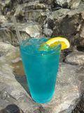 Blue Hawaiian. Blue tropical drink with a waterfall background Stock Images