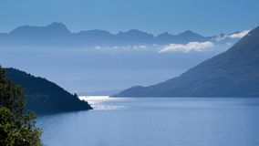 Blue Haze over Lake Wakatipu and Remarkables Mountains. View of Remarkables mountain range over Lake Wakatipu near Queenstown, New Zealand in blue Early Morning Royalty Free Stock Photos