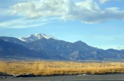 Blue Haze and Pike's Peak. Beautiful blue haze covers majestic Pike's Peak.  Snow caps and fluffy white clouds.  Golden meadow and blue skies Stock Photos