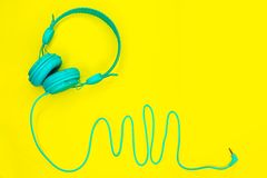 Blue headphones lie on a colorful yellow background with copy space stock photo