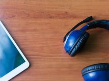 Blue headphones and tablet on the table royalty free stock photo