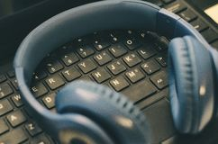 Blue headphones over a black keyword. It is a close up photo. stock images
