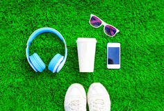 Blue headphones, white smartphone, cup of fruit juice with sneakers shoes, sunglasses on a green grass textured background Stock Photos