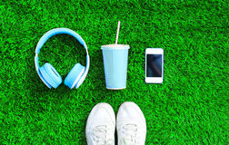 Blue headphones, white smartphone, cup of fruit juice with sports sneakers shoes on a green grass textured background Royalty Free Stock Photography