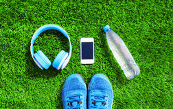 Blue a headphones and white smartphone with sports sneakers shoes, bottle of water on a green grass textured background Stock Image