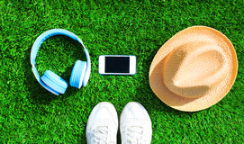 Blue headphones and white smartphone with straw hat on a green grass textured background, top view. Flat lay photo Stock Image