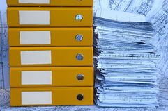 Blue heap of project drawings in yellow folder. Big heap of design and project drawings in yellow folder on the table surface. Blue whatman are background Stock Image