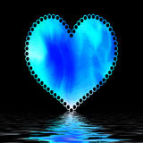 Blue heart on black. A view of a bright blue valentine heart with a lacy border against a black background and reflective, rippling water at the bottom Royalty Free Stock Image