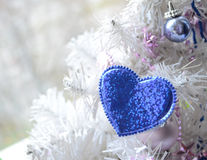 Blue heart hanging on artificial Christmas tree branch. Christmas decor. Winter holidays, celebration concept.  Stock Images