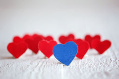 Blue heart and many red hearts on the white background. Valentin Stock Images
