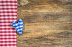 Blue heart and red checkered fabric on rustic wooden board. stock images