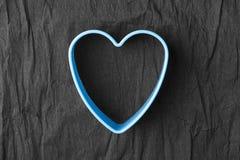 Blue heart shape on crumpled black paper stock image