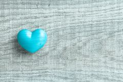 Blue heart shape over wooden table. Symbol of valentine day for royalty free stock photography