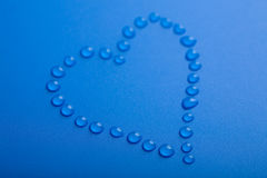 Blue heart shape of water droplets Royalty Free Stock Image