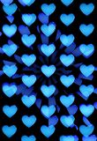 Blue hearts abstract. Burst of blue glossy hearts on black background Royalty Free Stock Images
