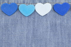 Blue hearts on denim background Stock Photos