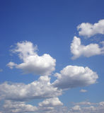 Blue heavens. On the blue sky freakish white clouds float Stock Photography