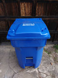Blue Heavy Duty Recycling Garbage Can. This residential, curbside plastic recycling container sits in a driveway, in front of a wooden garage door. This Royalty Free Stock Photos