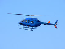 Blue helicopter. A blue helicopter flying in clear blue sky royalty free stock image