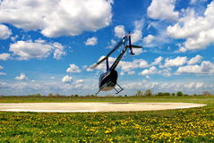 Blue helicopter. Taking off under a beautiful cloudy sky Royalty Free Stock Images