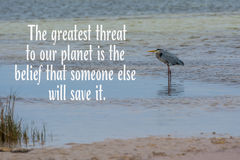 Blue heron on ocean with threat to planet quote. Blue heron waiting for a meal on beach with greatest threat to planet is the belief that someone else will save Royalty Free Stock Images