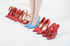 In Blue High Heels Amid Red Shoes Royalty Free Stock Images