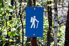 A blue hiking trail marker on a tree Stock Photos