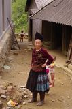 Blue Hmong ethnic woman. Woman of the Hmong blue outside his house. Children are barefoot Royalty Free Stock Photography