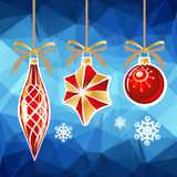 Blue holiday background. Three Christmas toys on a blue polygonal background Royalty Free Stock Photo