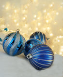 Blue Holiday Ornaments. Blue and silver holiday balls with warm starry background Royalty Free Stock Photo