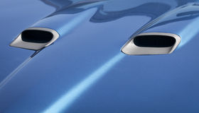 Blue Hood. Closeup of hood of a blue automobile with air intakes royalty free stock photography
