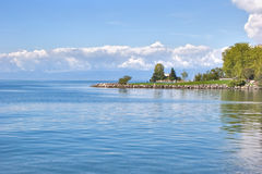 Blue horizon. Green cape on lake Leman in Switzerland Royalty Free Stock Photo